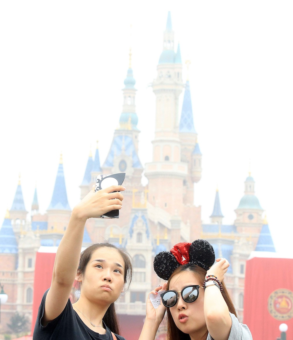 SHANGHAI, CHINA - JUNE 16: Tourists take a selfie at Shanghai Disney Resort on June 16, 2016 in Shanghai, China. Shanghai Disney Resort held the opening ceremony and welcomed tourists on Thursday. (Photo by Visual China/Getty Images)